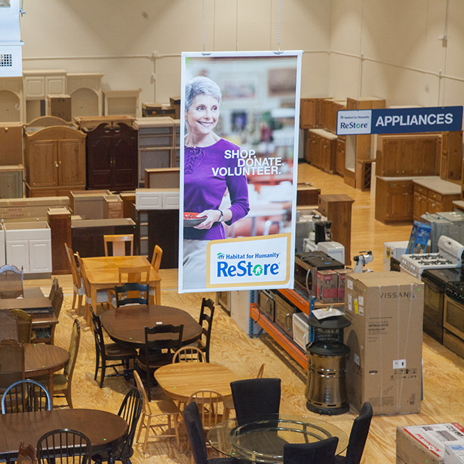 Habitat ReStore dining room furniture section with advertising banner above it
