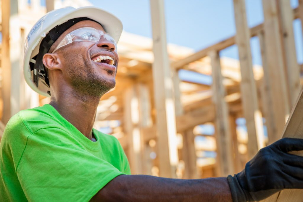 Smiling volunteer working on framing a Habitat home