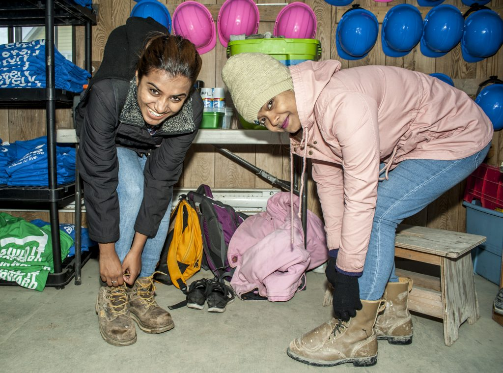 2 volunteers putting on workboots on a Habitat build site